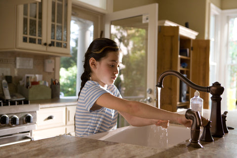 Girl washing hands on a counter sink