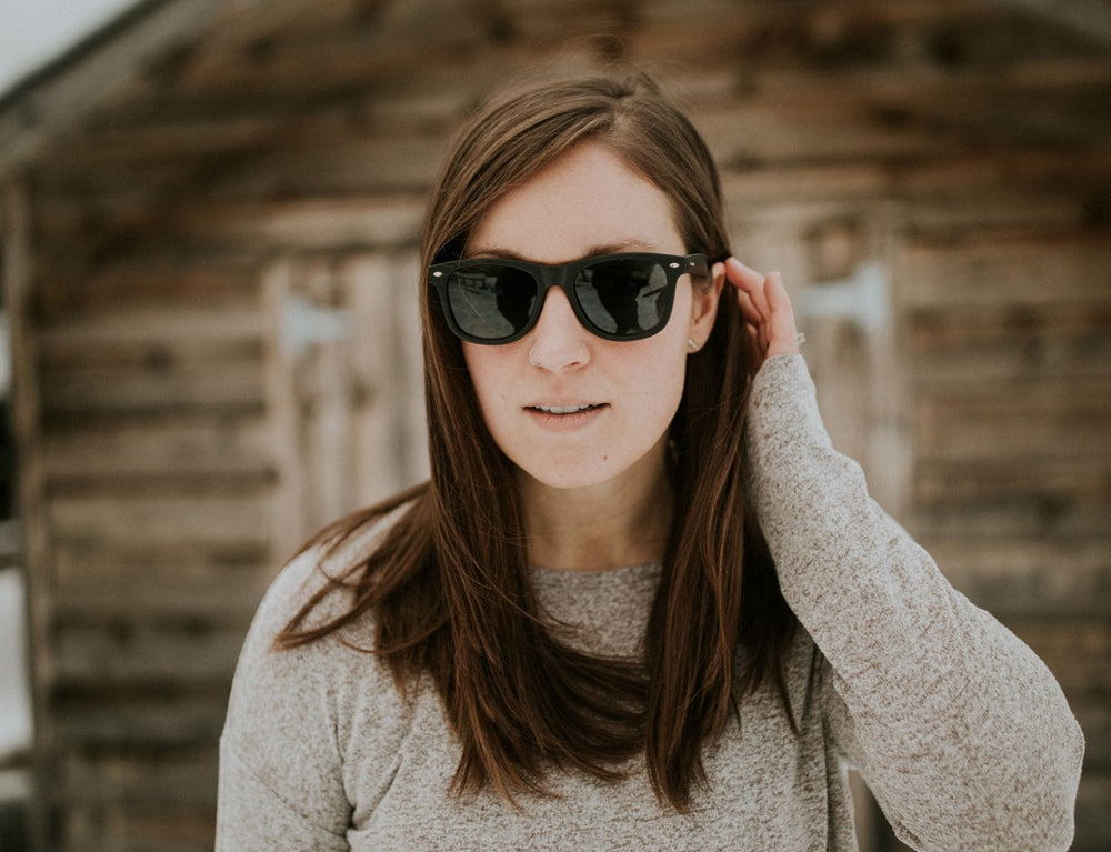 Woman wearing Black spartan frame sunglasses with gold accents