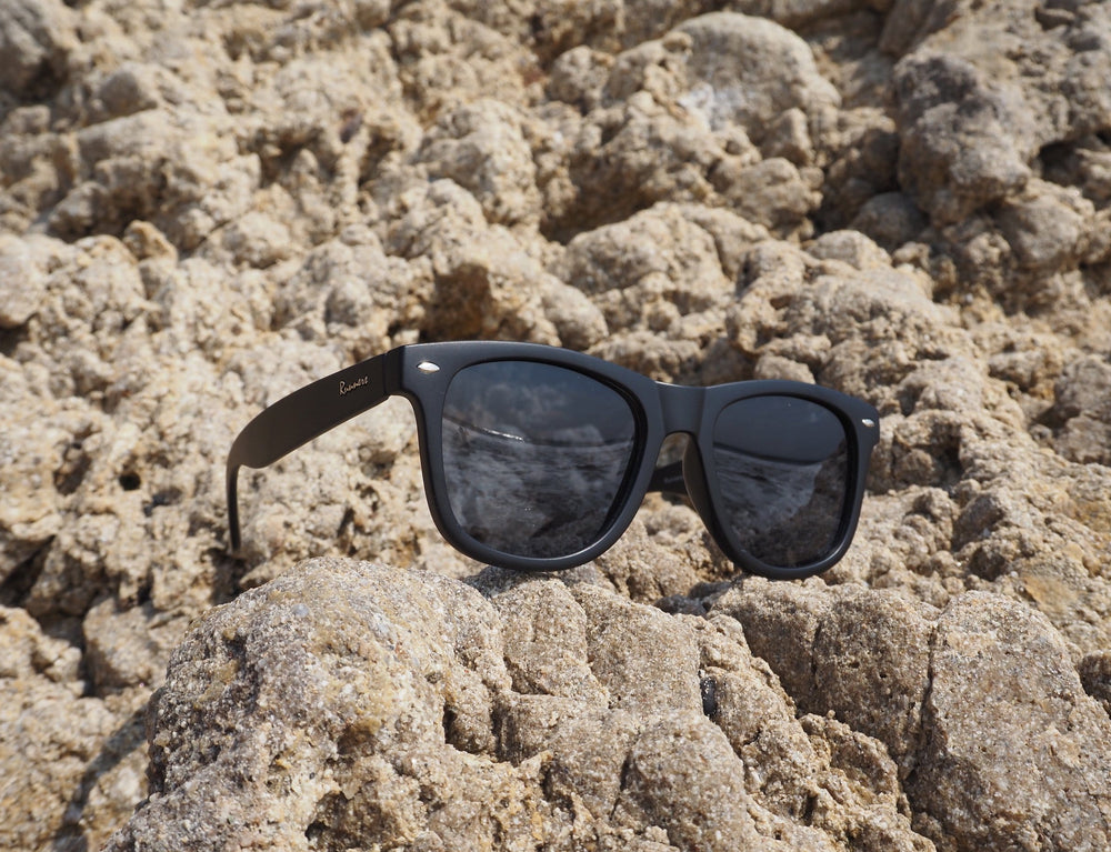 Black sunglasses with silver accents on the beach