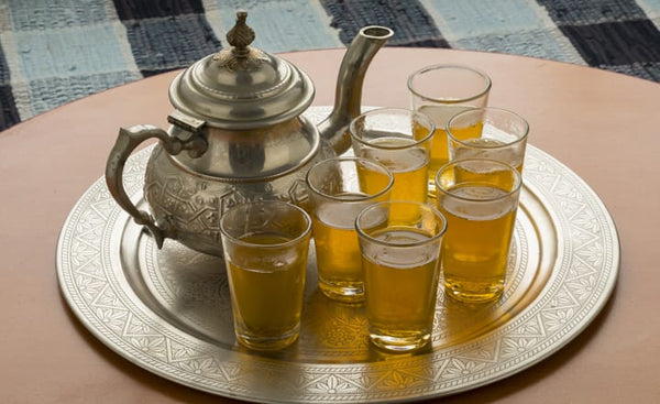 a tray with several glasses of Moroccan tea and teapot