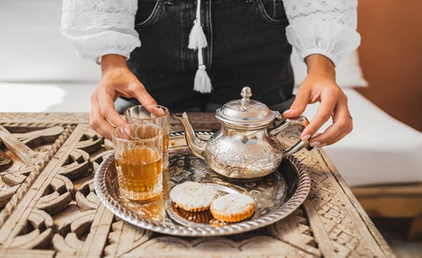 a woman serving Moorish tea in a glass with some pastries