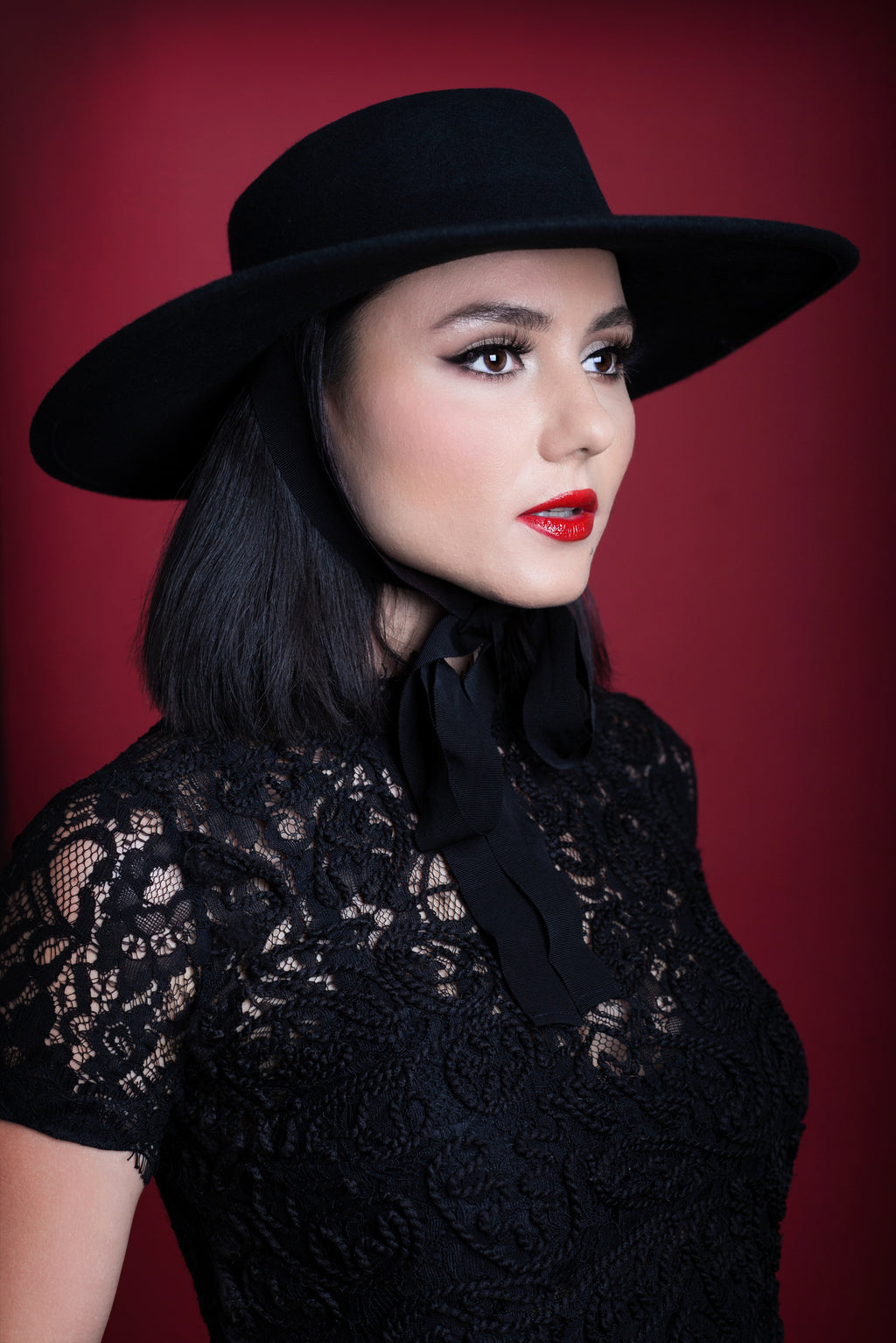A pinup model posing against a red backdrop while wearing a black, wide brim American Gothic hat.