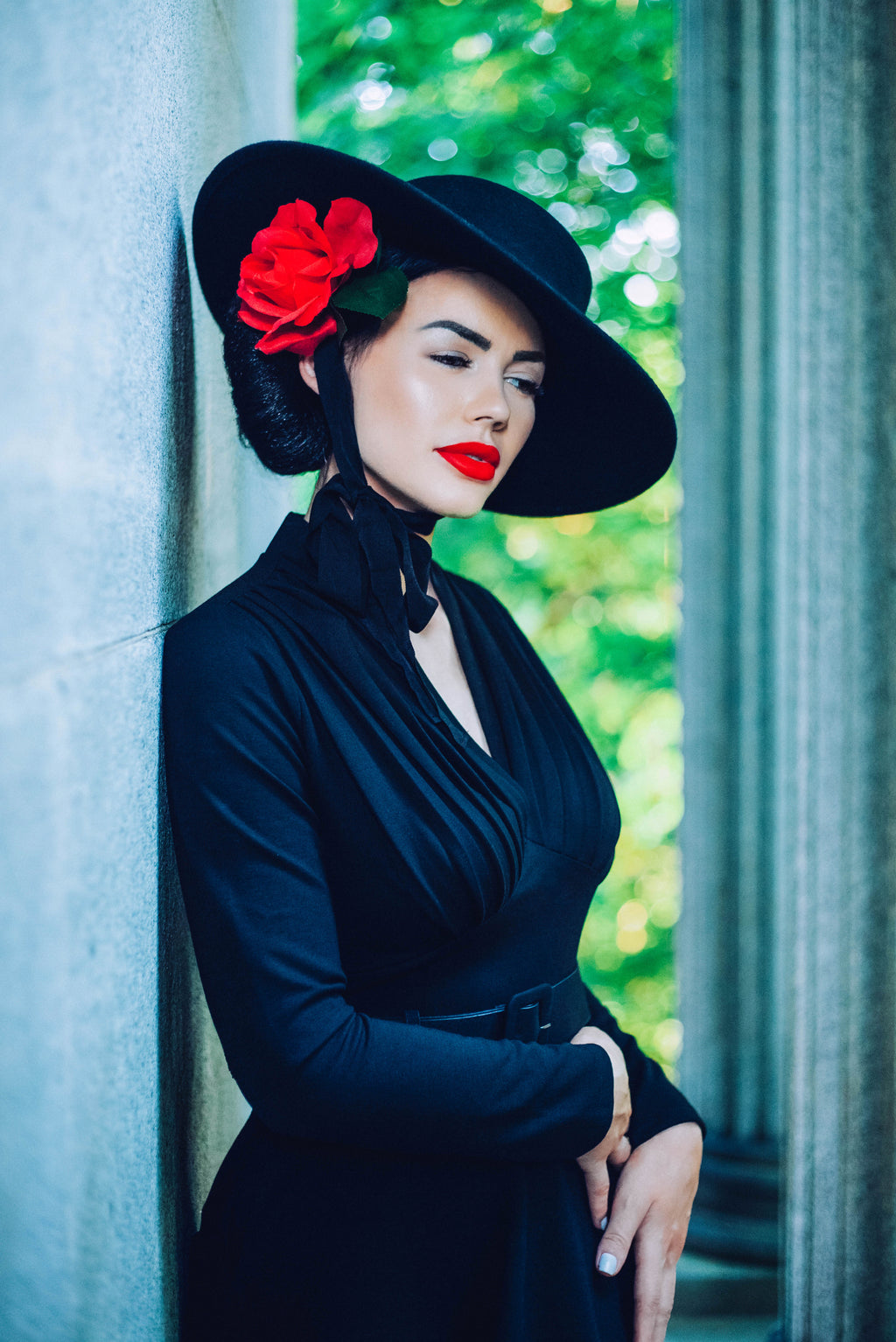 A  dark haired pinup model wearing the black, American Gothic wide brim wool hat.