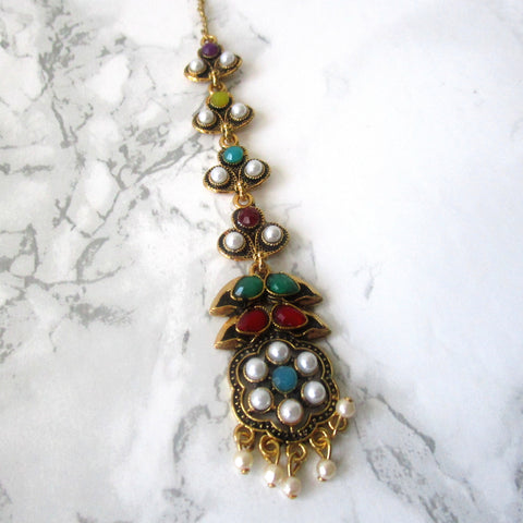Gorgeous Flower Tikka with white, blue, green red and gold detail.