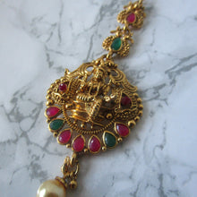 Load image into Gallery viewer, Hindu goddess tikka in gold with faux emeralds and rubies and a faux pearl. Perfect maang tikka/hair accessory to make a statement.