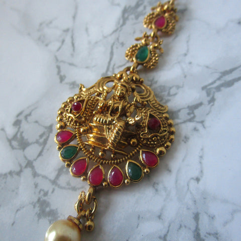 Hindu goddess tikka in gold with faux emeralds and rubies and a faux pearl. Perfect maang tikka/hair accessory to make a statement.