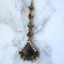 Load image into Gallery viewer, Muilticoloured tikka with gold, purple, green, blue, red and faux pearl detail. This statement piece is perfect for special occasions and parties.