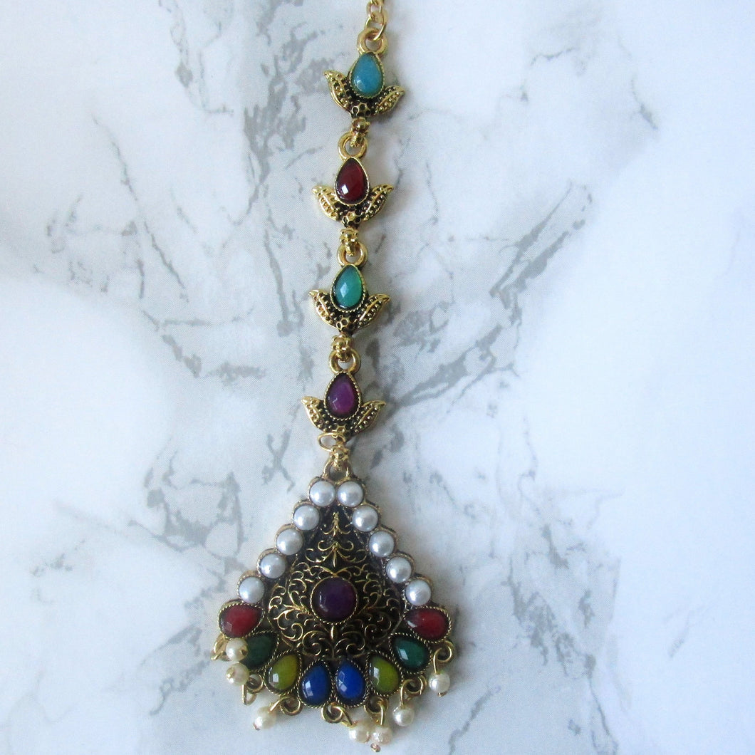 Muilticoloured tikka with gold, purple, green, blue, red and faux pearl detail. This statement piece is perfect for special occasions and parties.