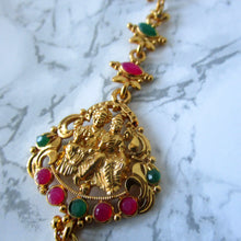 Load image into Gallery viewer, Temple themed tikka with HIndu God and Goddess on the front in Gold with faux ruby and emerald detailed and a faux pearl at the bottom. A maang tikka guaranteed to make a statement. Beautiful piece of hair jewellery/accessory.