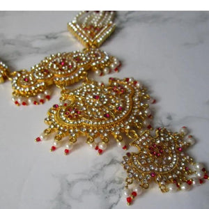 Truly beautiful and regal rani haar necklace with gold, faux pearl and faux ruby detail to really make a statement. This necklace is perfect for special occasions.