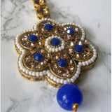 Gold and blue large flower tikka with faux pearl detail. This statement piece is perfect for special occasions and parties.