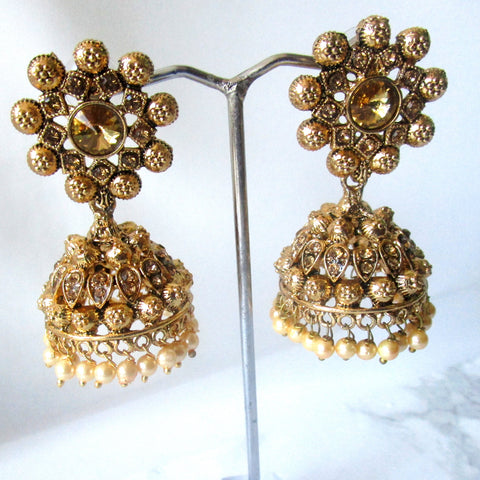 Beautiful statement gold flower jhumki earrings sure to make a statement at parties, weddings and any other special occasion. These earrings are the perfect touch of glamour to help you make a real statement.
