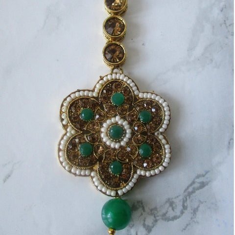 Gold and green large flower tikka with faux pearl detail. This statement piece is perfect for special occasions and parties.