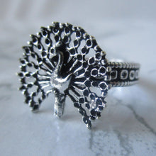 Load image into Gallery viewer, Detailed in shape and design. This gothic ring has a beautiful peacock with fanned out peacock feathers on the face. The ring is adjustable, and will fit all ring sizes. This ring is perfect for everyday or a special occasions.