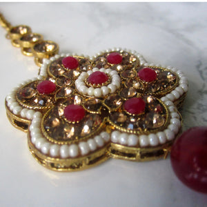 Gold and red large flower tikka with faux pearl detail. This statement piece is perfect for special occasions and parties.