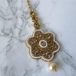 Gold and white large flower tikka with faux pearl detail. This statement piece is perfect for special occasions and parties.