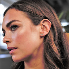 A female model wearing ear piercing jewellery in her left ear lobe - the lower stud is a gold six point star, the stud above is a small crystal stud.