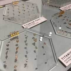 A selection of gold and silver piercing jewellery available at Liars & Lovers' London ear piercing studio, including sparkly studs with crystal embellishment