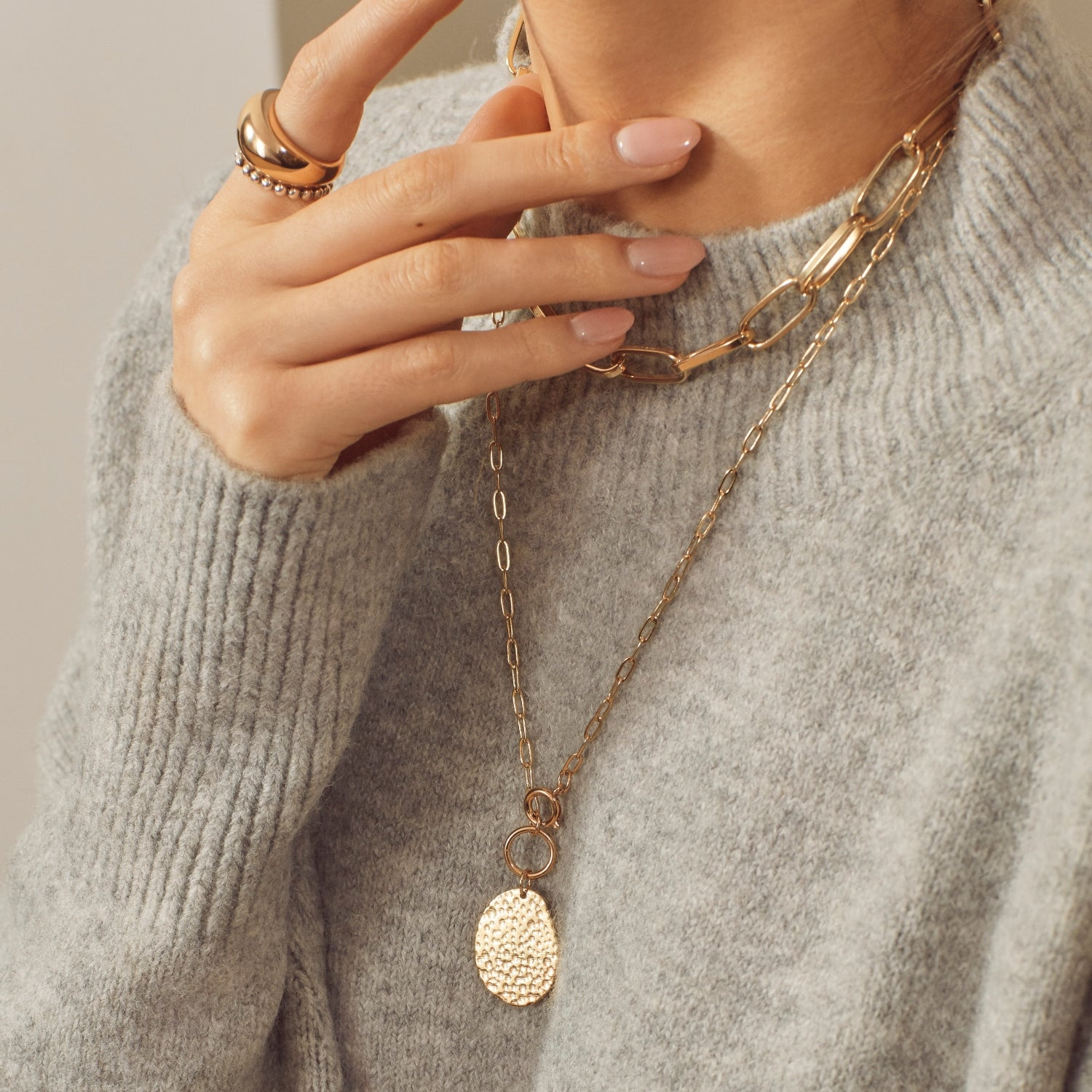 Girl in a grey jumper wearing a multirow chunky chain and pendant gold necklace and a gold dome ring
