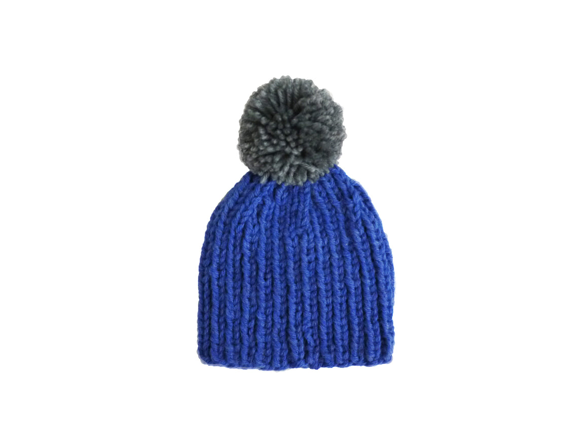 blue knitted hat with grey pompom