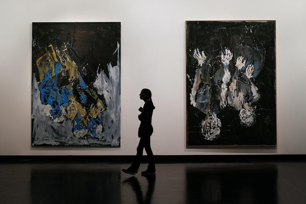 person in an art gallery in front of two large paintings