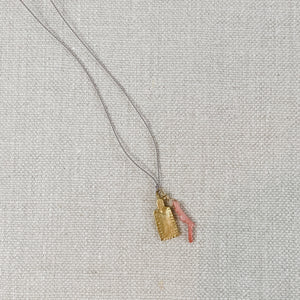 Pink coral and gold tag charm necklace, strung on grey silk cord.