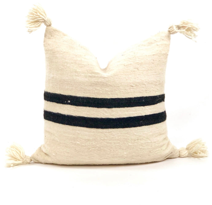 Cream wool pillow with bold double black stripe and corner poms
