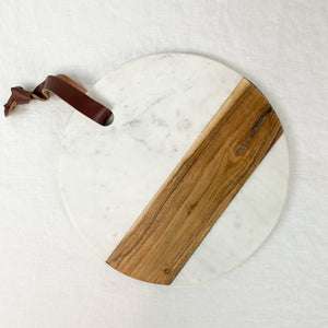 "Round white marble and natural wood serving board. Measures 12"" diameter, has leather strap for hanging."