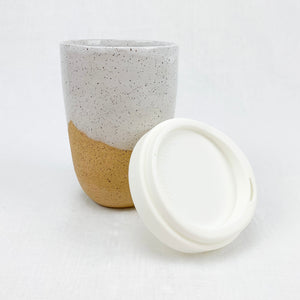 Natural stoneware travel mug with white speckled glaze. Comes with silicone lid, holds 14 oz.