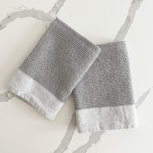 "Set of 2, grey waffle weave kitchen towels are a modern essential. Soft and absorbent, made from 100% cotton. Ends are finished with a woven twill border in white. Measures 28""L  18""W."