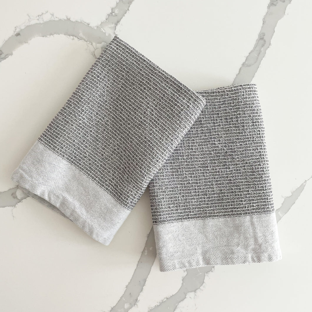 Set of 2, grey waffle weave kitchen towels are a modern essential. Soft and absorbent, made from 100% cotton. Ends are finished with a woven twill border in white. Measures 28