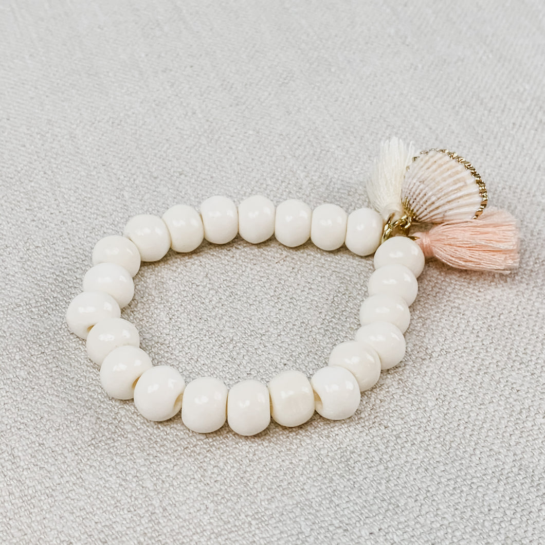 Stretch bracelet made with ivory beads, a gold dipped shell charm and mini blush & ivory tassels.