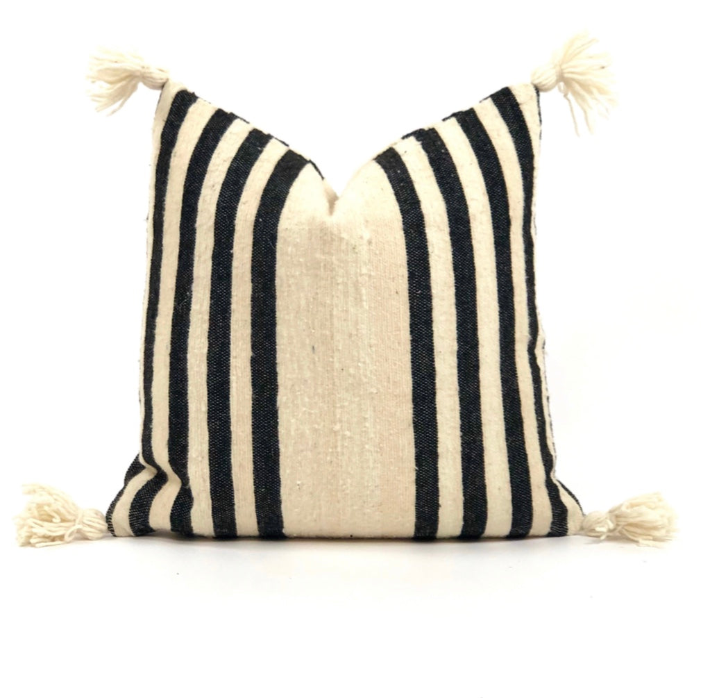 Natural cream wool pillow with bold black stripes and corner poms
