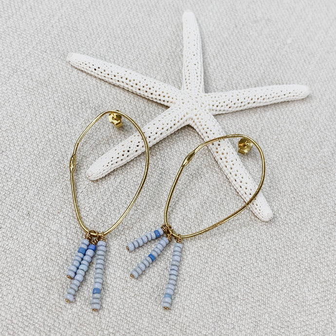 Gold plated hoop earrings with post back strung with 3 rows of pale blue glass beads. By Takara Jewelry.