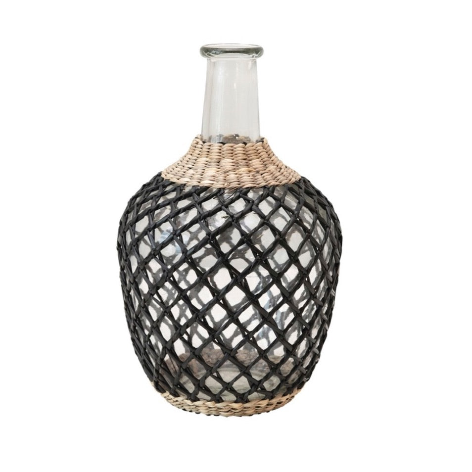 Mediterranean Seagrass Decanter. Glass bottle is wrapped in hand woven black and natural seagrass cage. Measures 10.25