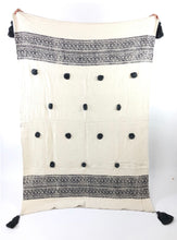 "Load image into Gallery viewer, The Ira Throw lends boho sophistication to your room. The cream slub cotton throw is block printed with an intricate black border and finished with handmade black poms and tassels. Artisan made, limited edition piece. Measures 49"" x 73""."