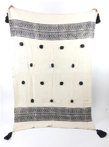Cream cotton throw with dark grey wood block print border and handmade poms