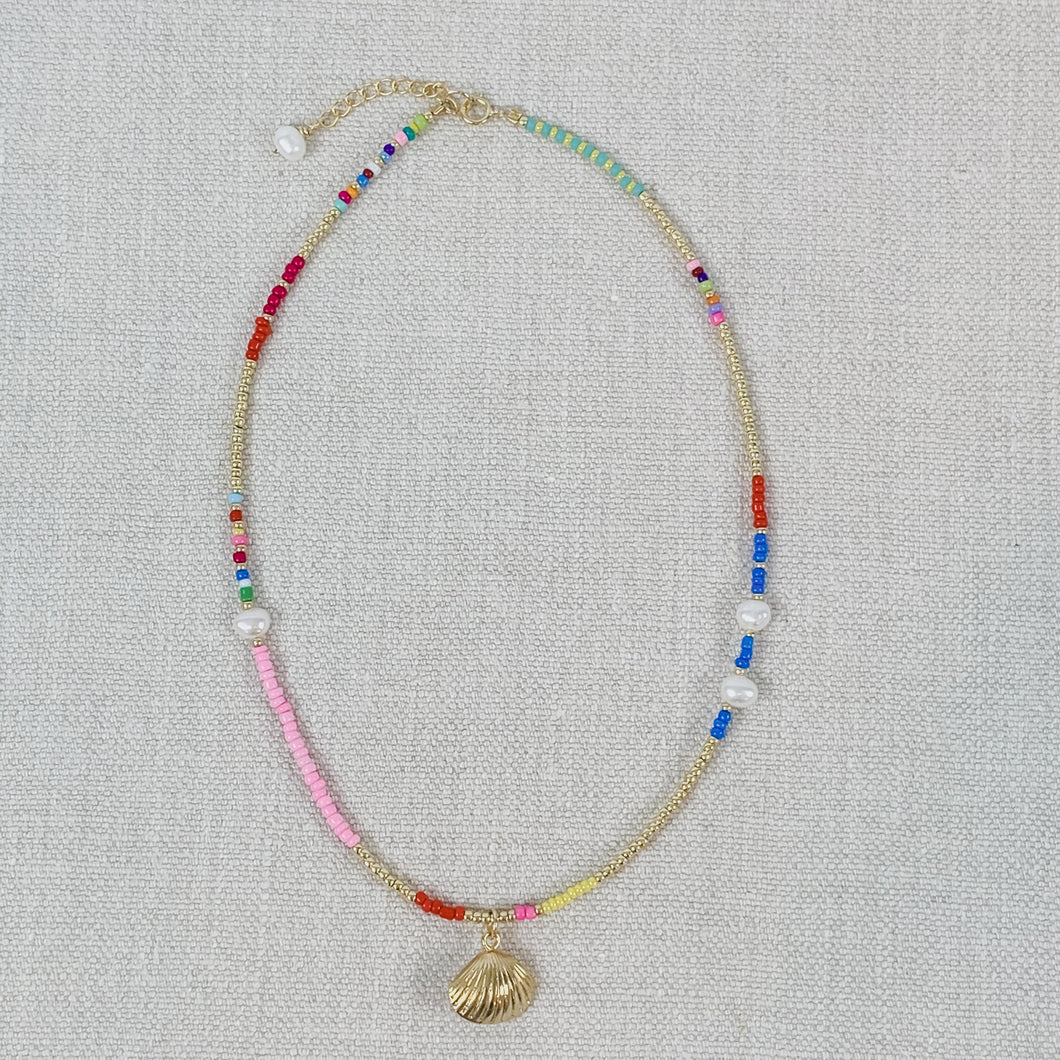 Beaded choker necklace made from rainbow seed beads and pearls. Finished with a gold plated seashell charm.