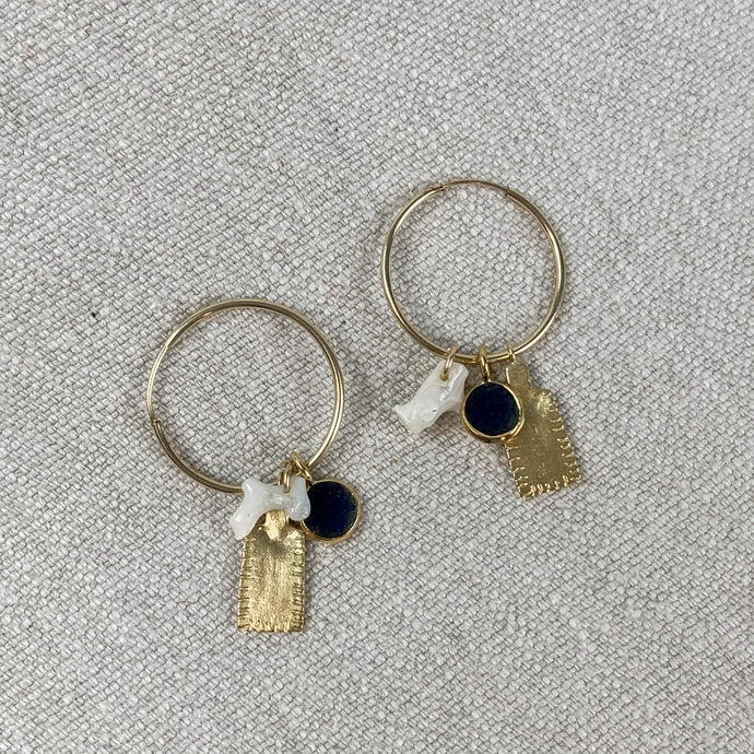 Gold plated hoop earrings with white coral, blue lapis and gold tag charms. By Takara Designs.