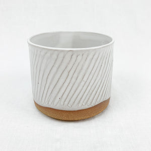 Small stoneware planter in natural clay with a white glaze. Hand carved texture.