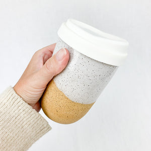 14 oz stoneware travel mug in natural clay with white speckled glaze. Comes with silicone lid.