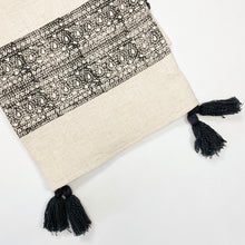 "Load image into Gallery viewer, The Ira Throw is the perfect way to layer on boho sophistication. Artisan made, limited edition piece. The cream slub throw is block printed with an intricate black border and finished with hand made black poms and tassels. Measures 49"" x 73""."