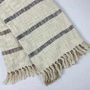Cotton throw, cream ground with brown and black stripes on reverse side.