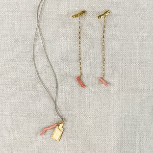 Delicate gold chain drop earrings with pink coral charm shown with coordinating necklace. By Takara jewelry.