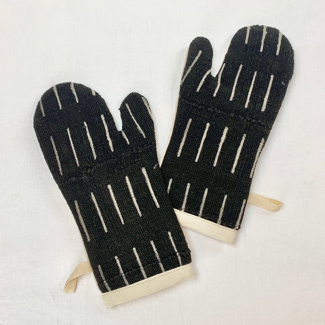 two black and cream oven mitts in African mud cloth