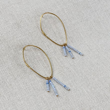 Load image into Gallery viewer, Gold plated hoop earrings with post back, strung with three rows of tiny pale blue glass beads. By Takara Jewelry.
