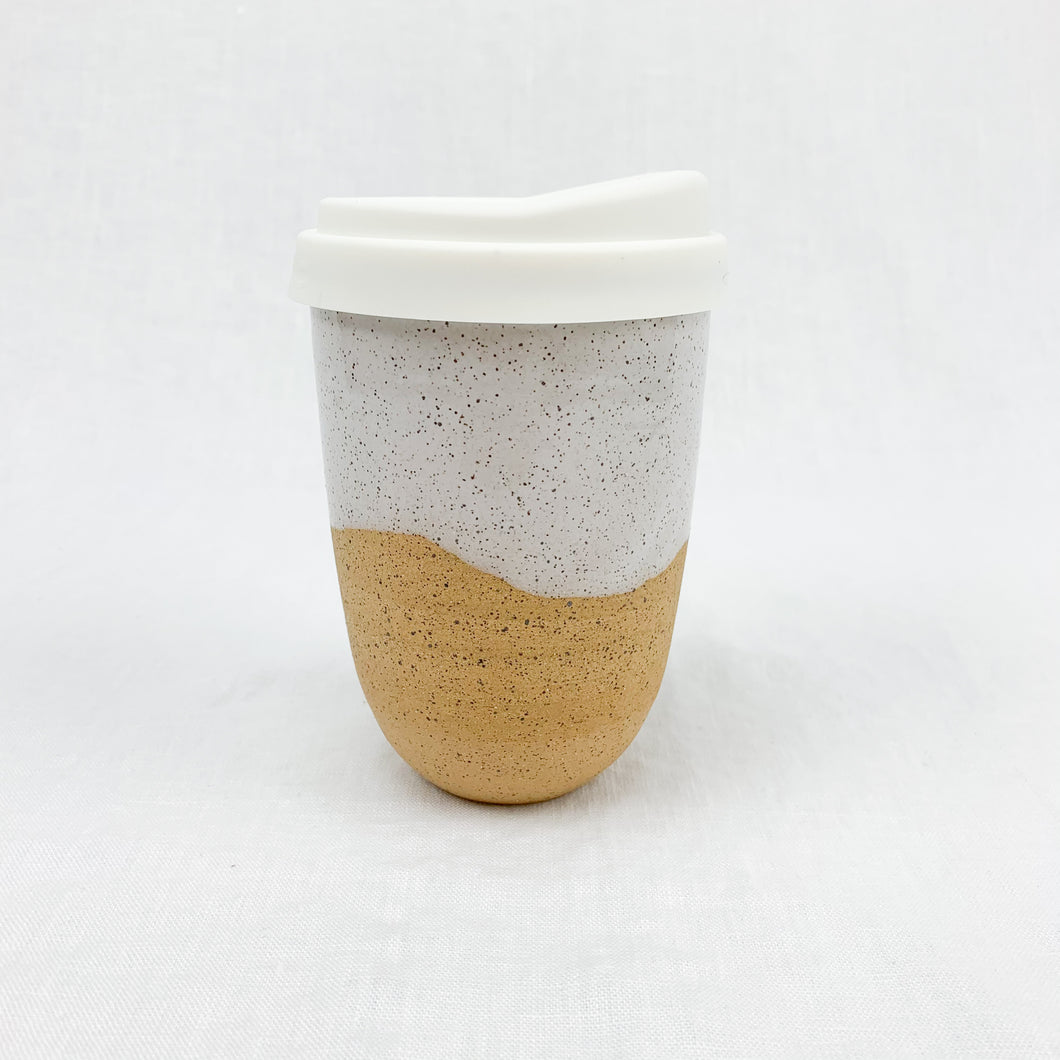 Travel mug with silicone lid. Made from natural stoneware with white speckled glaze. Holds 14 oz.