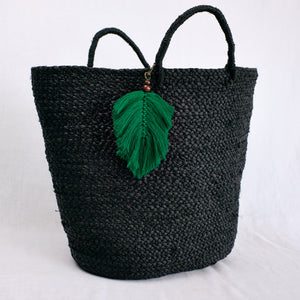 green palm frond charm shown on beach bag