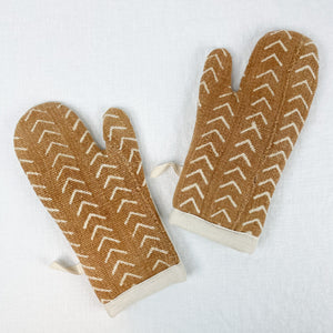 Pair of rust colored mud cloth oven mitts with natural cotton backing.