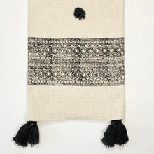 "Load image into Gallery viewer, The Ira Throw is the perfect way to layer on some boho sophistication. The cream slub cotton throw is block printed with an intricate black border and finished with handmade black poms and tassels. Artisan made, limited edition. Measures 49"" x 73""."